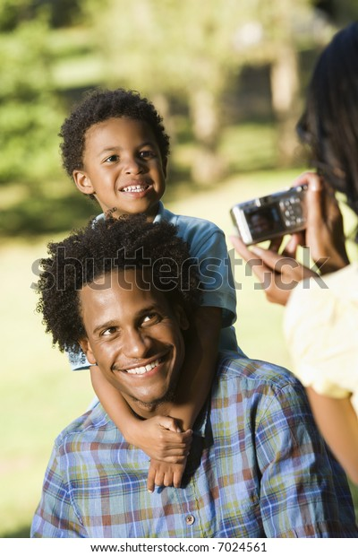 Father and son in park being photographed with digital camera.