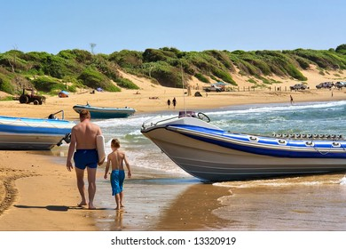 Father and son pass by boats on beach. Shot in Sodwana Bay, KwaZulu-Natal province, Southern Mozambique area, South Africa.