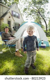 Father and son pitching a tent in the front yard