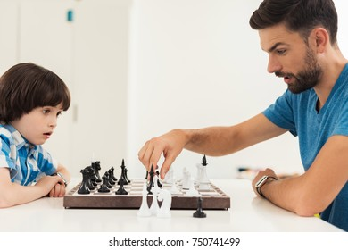 Father and son play chess in their home. They are sitting at a table by the window, in front of them there is a chessboard with chess pieces.