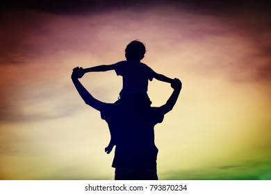 father and son play on sunset sky