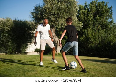 Father and son play soccer in the lawn of the home garden