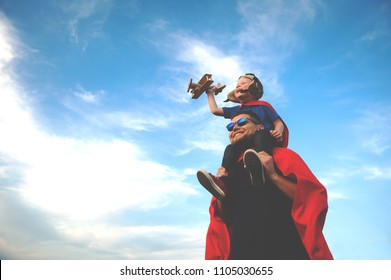 Father and son playing in aviator. Superman dad and son having fun. Imagination and dreams of being a pilot. Child pilot with airplane on dads back. Travel and vacation in summer. Freedom