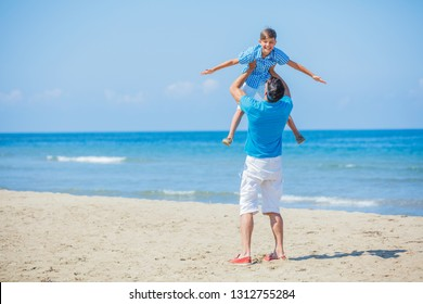 Father and son playing at beach together. Fun happy lifestyle