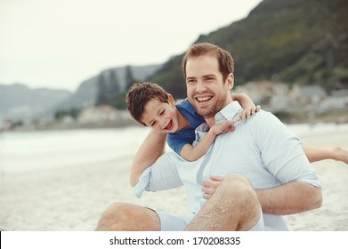 Father and son playing at beach together portrait fun happy lifestyle