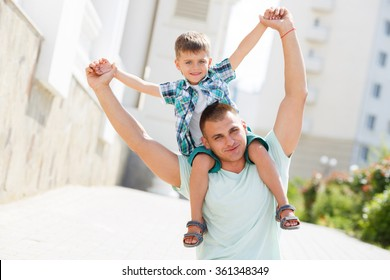 Father and son playing at beach together portrait fun happy lifestyle. Father holding son on his shoulders.