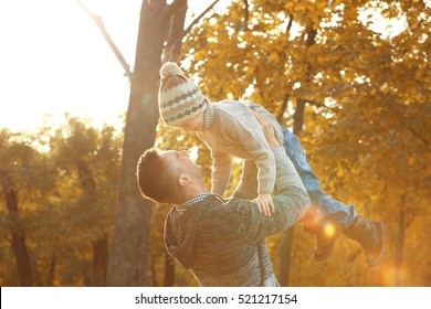 Father and son playing in beautiful autumn park