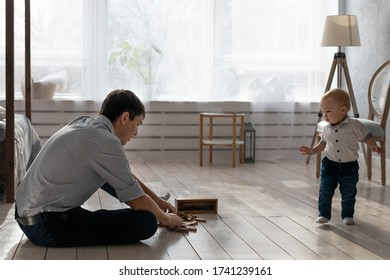 Father and son playing a Board game on the floor  in the bedroom next to the window. Father's day. A man on maternity leave