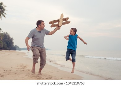 Father and son playing with cardboard toy airplane in the park at the day time. Concept of friendly family. People having fun outdoors on the beach.