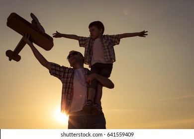 Father and son playing with cardboard toy airplane in the park at the sunset time. Concept of friendly family. People having fun outdoors.
