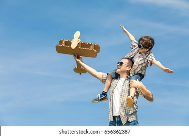 Father and son playing with cardboard toy airplane in the park at the day time. Concept of friendly family. People having fun outdoors. Picture made on the background of blue sky.