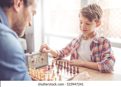 Father and son are playing chess and smiling while spending time together at home