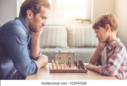 Father and son are playing chess while spending time together at home