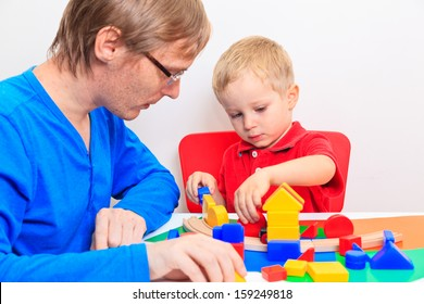 Father and son playing with colorful blocks at home