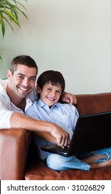 Father and son playing with a computer on the couch