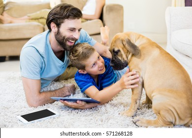 Father and son playing with a dog while using digital tablet at home