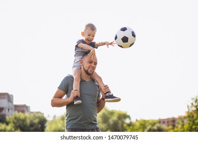 Father with son playing football at the field