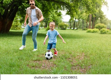 father and son playing football at park
