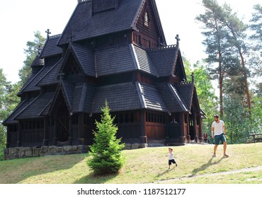 Father and son playing in front of the Gol Church,  a stave church originally built in Gol city, but now located in the Norwegian Museum of Cultural History at Bygdøy in Oslo, Norway.