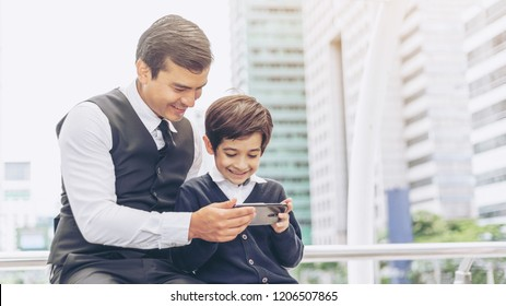 Father and son playing game smart phone together on business district urban, Dad and Son happy family concept