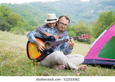 Father and son playing the guitar outdoors