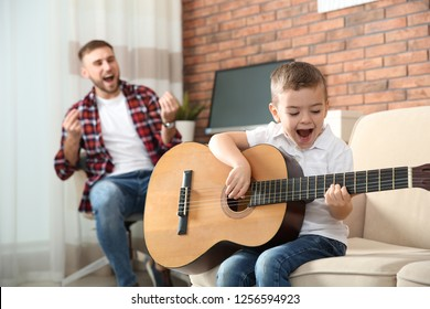 Father and son playing guitar and singing at home
