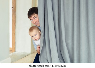 Father and son playing hide-and-seek. Father and son hiding behind a curtain in a room.