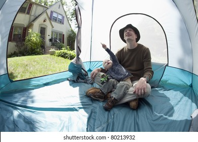 Father and son playing inside the tent in the front yard