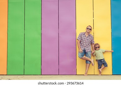Father and son playing near the house at the day time. They standing near are the colorful wall. Concept of friendly family.