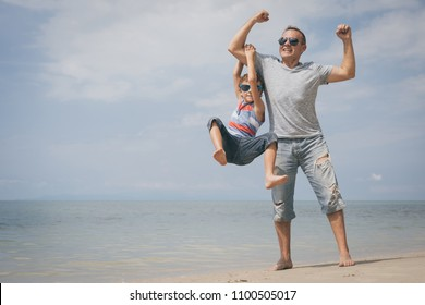Father and  son playing on the beach at the summer day time. People having fun outdoors. Concept of summer vacation and friendly family.