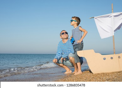 Father and son playing on the beach at the day time. They are dressed in sailor's vests. Concept of sailors on vacation and friendly family.