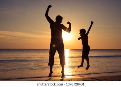 Father and son  playing on the beach at the sunset time. People having fun outdoors. Concept of summer vacation and friendly family.