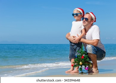 Father and son playing on the beach at the day time. Concept of Happy New Year.
