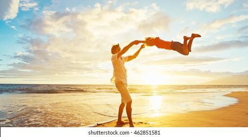 Vater und Sohn, die bei Sonnenuntergang am Strand spielen