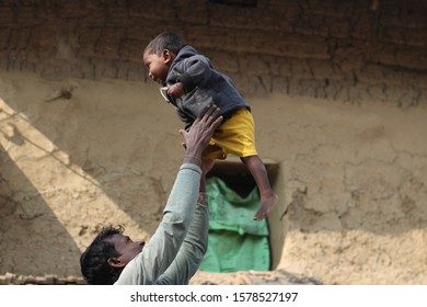Father and son playing on a beautiful morning. Father throwing his son in the air for the joy of his son. Young farmer playing with an infant in a morning of winter. Farmer family enjoying a nice day.