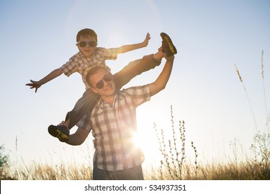 Father and son playing on the field at the day time. People having fun outdoors. Concept of friendly family.