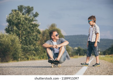 Father and son playing on the road at the day time. People having fun outdoors. Concept of friendly family.