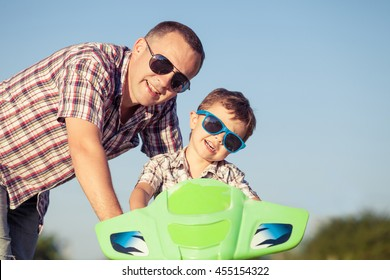 Father and son playing on the road at the day time. They driving on quad bike in the park. People having fun on the nature. Concept of friendly family.