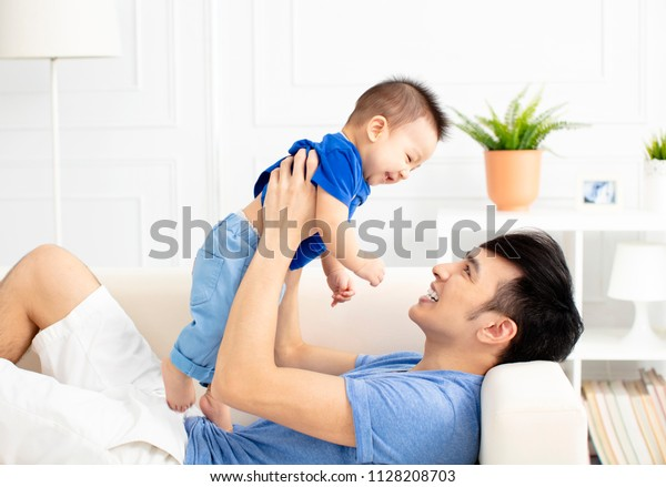 Father And Son Playing On Sofa Together