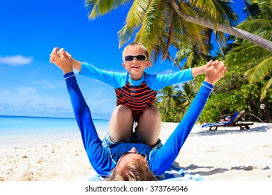 father and son playing on summer beach