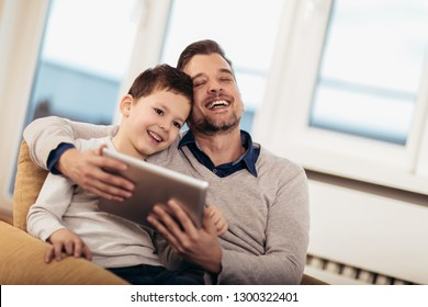 Father and son playing on a tablet at home, having fun, selective focus.