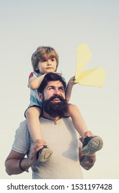 Father and son playing outdoors. Weekend family play. Portrait of happy father giving son piggyback ride on his shoulders and looking up