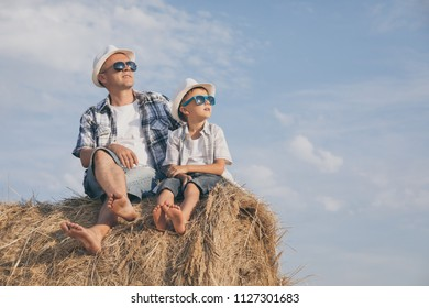 Father and son playing in the park at the day time. People having fun outdoors. Concept of summer vacation and friendly family.
