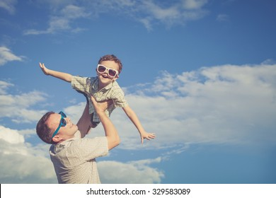 Father and son playing in the park  at the day time. Concept of friendly family. Picture made on the background of blue sky.