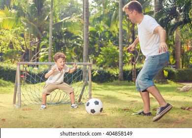 Father and son playing in the park  at the day time. Concept of friendly family. Picture made on the green meadow.