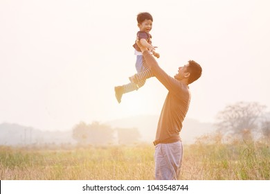 Father and son playing in the park at the sunset time