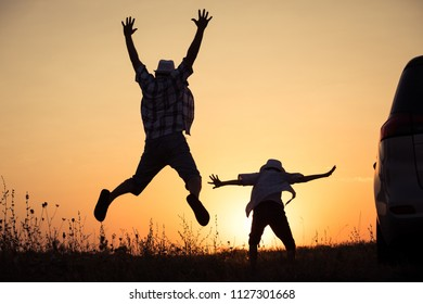 Father and son playing in the park at the sunset time. People having fun outdoors. Concept of summer vacation and friendly family.