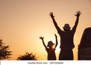 Father and son playing in the park at the sunset time. People having fun on the field. Concept of friendly family and of summer vacation.