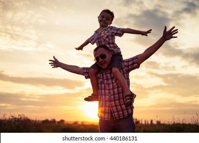 Father and son playing at the park at the sunset time. People having fun on the field. Concept of friendship forever and of summer vacation.