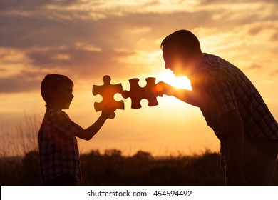 Father and son playing at the park at the sunset time. People having fun on the field. Concept of the kid is ready to go to school.